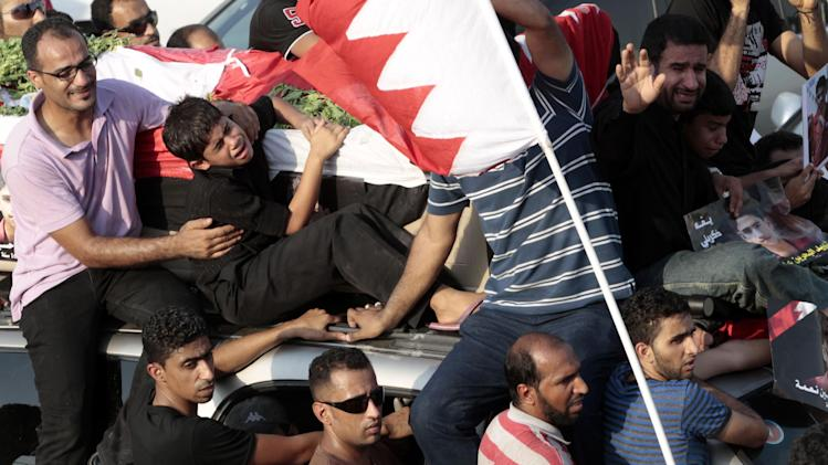 The casket carrying Ali Hussein Niema, 17, who allegedly was shot dead by riot police late Friday, is accompanied by his father, Hussein, seated holding a picture of his son on the front of the vehicle, and his younger brothers, crying beside the father and seated second left on vehicle, during a politically charged funeral procession attended by thousands in Sadad, Bahrain, on Saturday, Sept. 29, 2012. The death could bring fresh protests by Shiite-led groups seeking a greater political voice in the Sunni-ruled Gulf kingdom. (AP Photo/Hasan Jamali)