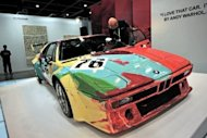 "An emplyee is seen polishing the windshield of a car painted by Andy Warhol at Asia's premier art fair ""Art HK,"" in Hong Kong, on May 16. Traditionally known as a centre of banking and finance, Hong Kong has become a hub of all things luxury -- from fine wine to fashion and, increasingly, art -- thanks to the explosion of personal wealth among mainland Chinese"