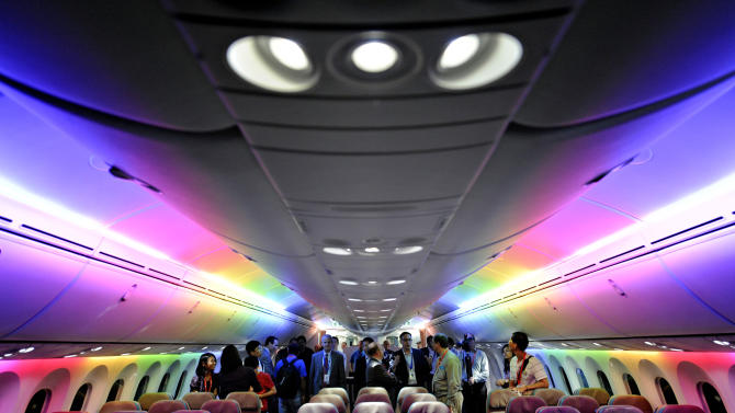 FILE - In this Feb. 12, 2012, file photo, members of the media tour Boeing 787 Dreamliner's cabin displaying versatile LED lighting system during a press preview in Singapore. While Boeing's 787 Dreamliners are grounded, the batteries causing airliner's troubles can still fly. At the time the government certified the 787 as safe, federal rules barred the type of batteries used to power the airliner's electrical systems from being carried as cargo on passenger planes because of the fire risk. But new rules exempt aircraft batteries from the ban on large lithium ion batteries as cargo on flights by passenger planes. (AP Photo/Bryan van der Beek, File)