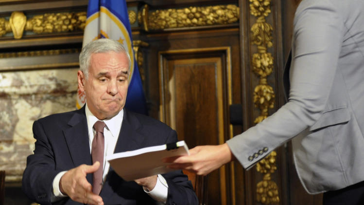 "Minnesota Gov. Mark Dayton is handed one of the bills as he signs the state budget bill which ends the government shutdown, Wednesday, July 20, 2011 in St. Paul, Minn. Dayton's signature came just hours after lawmakers gave their own approval to the deal after meeting in special session that started Tuesday afternoon and lasted until early Wednesday morning. After signing the budget, Dayton said he was ""not entirely happy"" with it. (AP Photo/Jim Mone)"