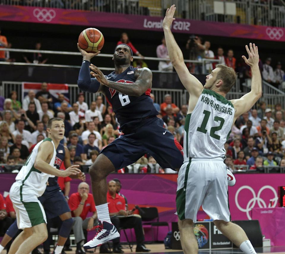 USA's Lebron James shoots as he drives past Lithuania's Antanas Kavaliauskas (12) during a men's basketball game at the 2012 Summer Olympics, Saturday, Aug. 4, 2012, in London. (AP Photo/Charles Krupa)