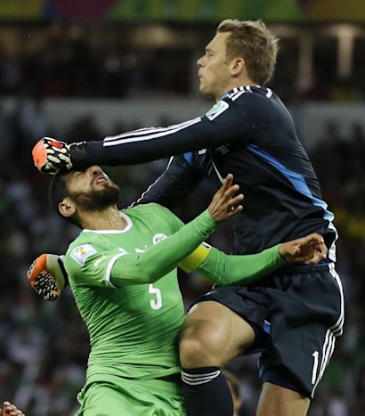 Germany's goalkeeper Manuel Neuer, right, hits Algeria's Rafik Halliche in the face after clearing the ball during the World Cup round of 16 soccer ma...