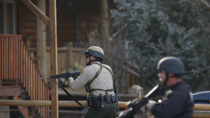 """San Bernardino County sheriff's deputies conduct door-to-door search in Big Bear, Calif, Thursday, Feb. 7, 2013.  Thousands of police officers hunted Thursday for one of their own: a former Los Angeles officer angry over his firing and sought in a deadly shooting rampage after warning he would wage """"warfare"""" on those who wronged him, authorities said. (AP Photo/Jae C. Hong)"""