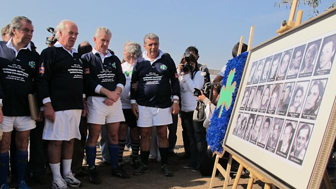 Former members of Uruguay's rugby team who survived a 1972 plane crash in the Chilean Andes hold a minute of silence after the unveiling a plaque with pictures of family members and friends who died in the crash, in Santiago, Chile, Saturday, Oct. 13, 2012. Uruguay's former rugby players marked the 40 year anniversary since they survived 72 days in the Chilean Andes by playing a rugby match with the former members of Chile's team. Only 16 of the 45 passengers aboard survived, by feeding on dead passengers preserved in the snow. (AP Photo/Luis Andres Henao)