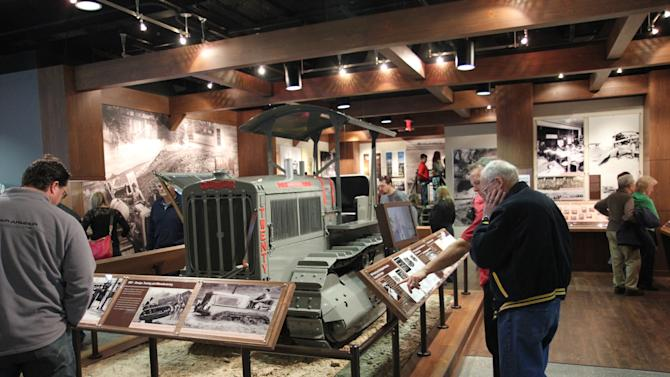 This December 2012 photo shows people touring the Caterpillar Visitors Center in Peoria, Ill. Caterpillar Inc. manufactures heavy equipment that bulldozes, digs, lifts and performs other tasks at construction and mining sites. The center lets visitors climb inside the machines for a closer look while computer simulations provide an opportunity to learn how to manipulate the controls. (AP Photo/Fritz Faerber)