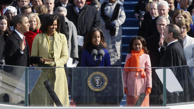 FILE - In this Jan. 20, 2009 file photo, Barack Obama, left, joined by his wife, Michelle, second from left, and daughters Malia, third from left, and Sasha, takes the oath of office from Chief Justice John Roberts to become the 44th president of the United States at the U.S. Capitol in Washington. Obama will raise his right hand and place his left on a Bible as he takes the oath of office for a second four-year term. His second inauguration promises the pageantry of the first, but on a smaller scale than 2009, when a record 1.8 million people filled the nation's capital to witness Obama making history as America's first black president. (AP Photo/Ron Edmonds, File)