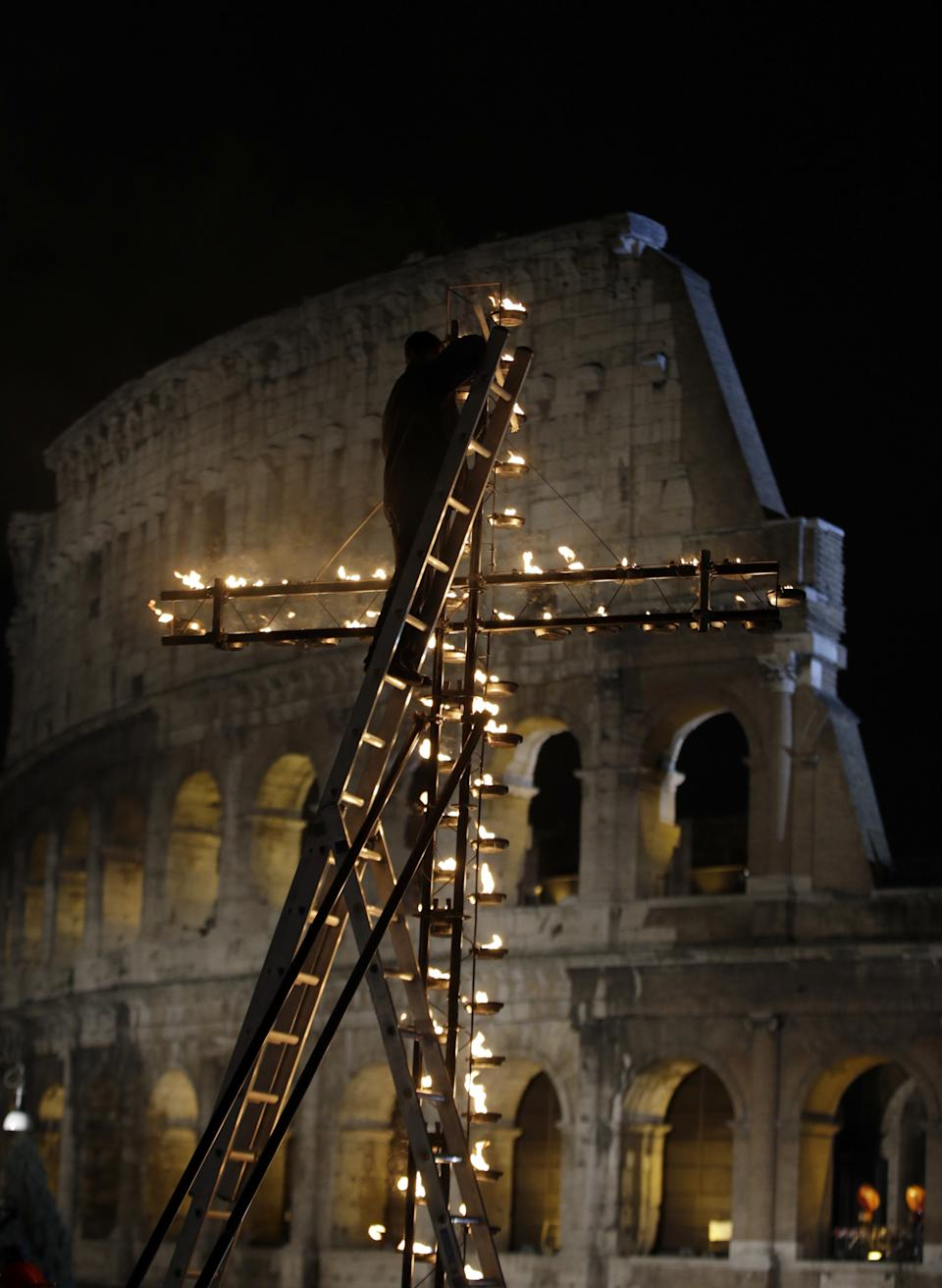 A worker adjusts a giant torch lit cross overlooking the ancient Colosseum prior to the start of the Via Crucis (Way of the Cross) torchlight procession which will be celebrated by Pope Francis, on Good Friday, in Rome, Friday, March 29, 2013.  (AP Photo/Andrew Medichini)