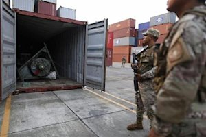 Panama police officers stand guard at containers holding arms seized from a North Korean flagged ship in Colon City
