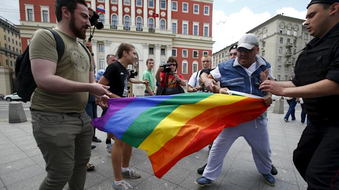 Anti-gay protesters try to tear rainbow flag during LGBT community rally in central Moscow