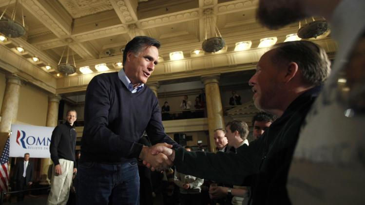Republican presidential candidate former Massachusetts Gov. Mitt Romney, accompanied by Sen. John Thune, R-S.D., left, greets residents during a caucus day rally at the Temple for Performing Arts, Tuesday, Jan. 3, 2012, in Des Moines, Iowa. (AP Photo/Charlie Neibergall)