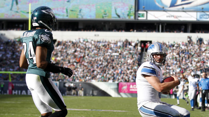 Detroit Lions quarterback Matthew Stafford, right, scores on a one-yard run as Philadelphia Eagles cornerback Nnamdi Asomugha defends during the second half an NFL football game, Sunday, Oct. 14, 2012, in Philadelphia. (AP Photo/Mel Evans)