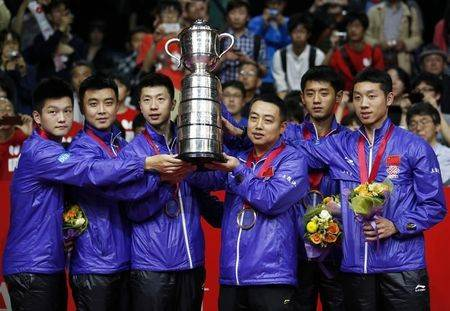 China's Fan, Wang, Ma, coach Liu, Zhang and Xu pose with the world championships trophy as they celebrate their victory against Germany at the World Team Table Tennis Championships in Tokyo