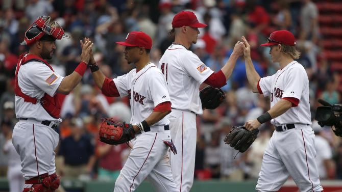 Boston Red Sox's Clay Buchholz, second from right, celebrates with teammates, from left, Sandy Leon, Mookie Betts and Brock Holt after defeating the Houston Astros 6-1 in a baseball game in Boston, Saturday, July 4, 2015. (AP Photo/Michael Dwyer)