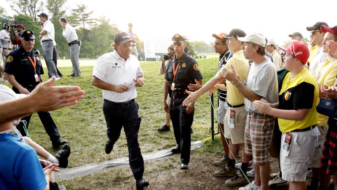 Phil Mickelson jogs off the 18th green after the third round of the U.S. Open golf tournament at Merion Golf Club, Saturday, June 15, 2013, in Ardmore, Pa. (AP Photo/Gene J. Puskar)