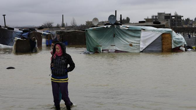 Hiam al-Hussein, 23, from Syria's war ravaged Homs district of Baba Amr, stands in flooded water at a temporary refugee camp, in the eastern Lebanese Town of Al-Faour near the border with Syria, Lebanon, Tuesday, Jan. 8, 2013. Two Syrian refugee encampments in Lebanon's eastern Bekaa valley  were completely immersed in water Tuesday after the Litani river flooded and the water came pouring into their tents. The flood forced dozens of Syrian refugees to leave in search for alternative shelter along with their water-soaked and muddied belongings. (AP Photo/Hussein Malla)