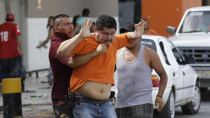 A man, center in orange, tries to prevent another one from storming a supermarket in Los Cabos, Mexico,  Tuesday, Sept. 16,  2014.  Employees of the supermarket said the company donated all the food at the market and established a system by which every person had 5 minutes to get whatever they could for free as fights broke outside with people inciting the crowd to loot. Desperate locals and tourists were in survival mode in the resort area of Los Cabos also on Wednesday, with electrical and water service still out three days after Hurricane Odile made landfall as a monster Category 3 storm.(AP Photo/Victor R. Caivano)