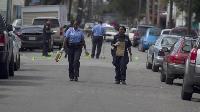 New Orleans Police investigate shooting at the intersection Frenchman Street at N. Villere on Mother's Day in New Orleans, Sunday May 12, 2013. Gunmen opened fire on dozens of people marching in a Mother's Day neighborhood parade in New Orleans on Sunday, wounding at least 17, police said. (AP Photo/Doug Parker)