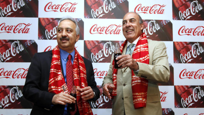Chairman and CEO of The Coca-Cola Co., Muhtar Kent, right, holds a bottle of Coca Cola and President and CEO of Coca Cola India and South West Asia Atul Singh pose for photos before the start of a meeting in New Delhi, India, Tuesday, June 26, 2012. The world's biggest beverage maker plans to invest US$5 billion in India from 2012 to 2020. It has already invested more than US$2 billion since re-entering the country in 1993. (AP Photo/Manish Swarup)