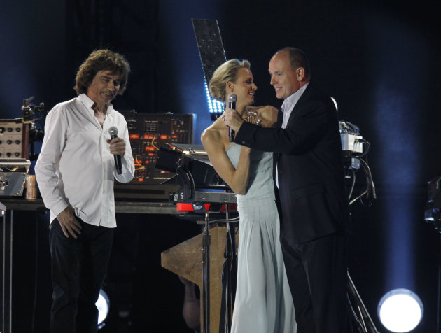 Prince Albert II of Monaco, right, and his bride Charlene Princess of Monaco, centre, dance onstage prior to a concert by French musician Jean-Michel Jarre, left, at the main port in Monaco, Friday, J