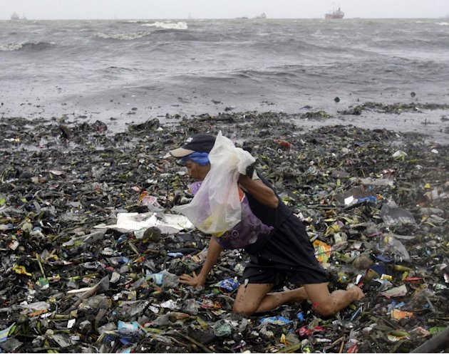 An old woman crawls on top of floating debris washed ashore due to Typhoon Nanmadol as she looks for salvagable materials Saturday, Aug. 27, 2011 in Manila, Philippines. Forecasters said the typhoon h