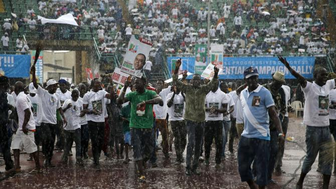 People hold campaign posters as it rains during a campaign for Nigeria's former military ruler and Presidential candidate of All Progressives Congress(APC) Muhammadu Buhari, in Lagos