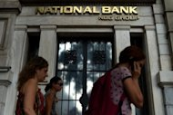 People pass a branch of the National Bank of Greece in Athens. Greece&#39;s banking sector is bracing for what local media called a super deal, following the announcement of the National Bank&#39;s offer to purchase the third-largest lender Eurobank