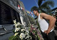 Bali bombing survivor, Australian Phil Britten, looks at the names of dead victims at a memorial monument to the victims of the attack in Kuta on the Indonesian resort island of Bali on October 9. The attacks on the heart of the nightlife strip, and another suicide blast in 2005 that killed 20 as they dined at the beachfront Jimbaran district, devastated the island&#39;s tourism industry