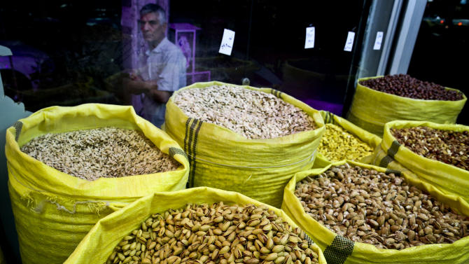 In this Sunday, March 31, 2013 photo, an Iranian man looks at nuts for sale at a nut shop, in western Tehran, Iran. Pistachios are Iran's top non-oil export and provide work for hundreds of thousands of people. Still, Iranian authorities are backing the boycott. They laud it as a way to decrease domestic pistachio consumption and leave more nuts for exporting, which has become an increasingly important pipeline for foreign revenue as sanctions squeeze Iran's oil and gas sales. (AP Photo/Ebrahim Noroozi)