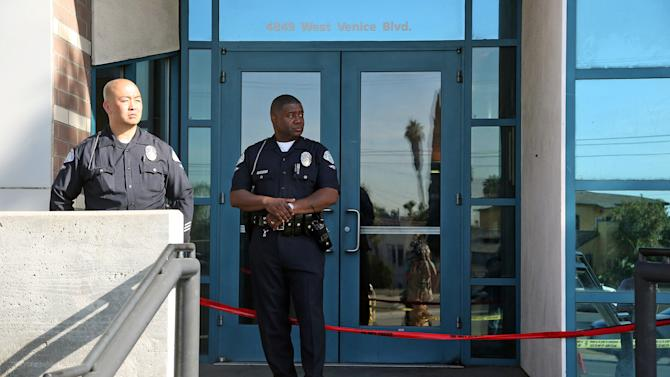 Los Angeles police officers stand outside the West Traffic Division station Tuesday, April 8, 2014, after an officer was shot and wounded inside the station Monday evening. A gunman who opened fire inside the police station, hitting one officer several times, was hospitalized early Tuesday in critical condition after he was wounded in the ensuing gunbattle, authorities said. (AP Photo/Nick Ut )