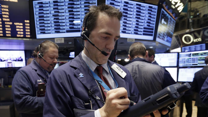 Trader Gregory Rowe, center, works on the floor of the New York Stock Exchange, Thursday, Dec. 19, 2013. Stocks edged lower in early trading Thursday, pulling back from record levels. (AP Photo/Richard Drew)