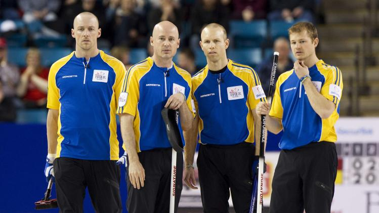 Team Alberta Nolan Thiessen, Kevin Koe, Pat Simmons and Carter Rycroft talk while facing team Quebec during the semi-final draw at the 2014 Tim Hortons Brier curling championships in Kamloops, British Columbia