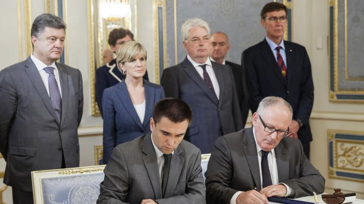 Dutch Foreign Minister Timmermans and Ukrainian Foreign Minister Klimkin sign documents during a meeting in Kiev