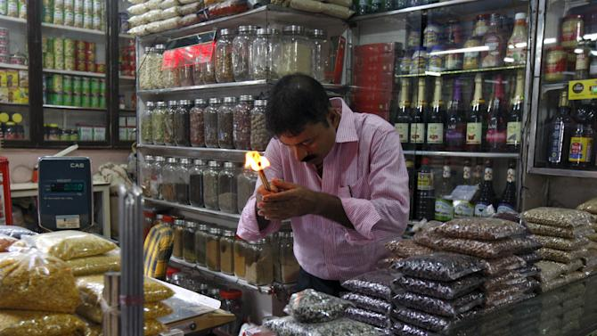 A shopkeeper holds burning incense as he prays inside his grocery shop before the start of his business day in Kolkata