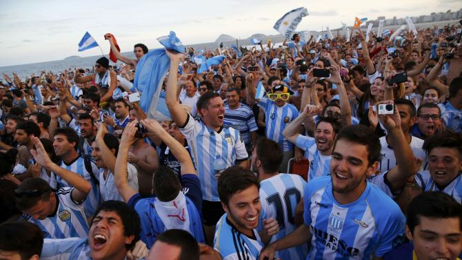 Argentina soccer fans react as they watch a broadcast of the 2014 World Cup semi-final between Argentina and the Netherlands at Copacabana beach in Rio de Janeiro