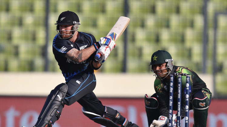 New Zealand captain Brendon McCullum, left, attempts a reverse sweep as Pakistan's wicketkeeper Kamran Akmal, right, takes his position during their ICC Twenty20 Cricket World Cup warm up match in Dhaka, Bangladesh, Monday, March 17, 2014. (AP Photo/Aijaz Rahi)