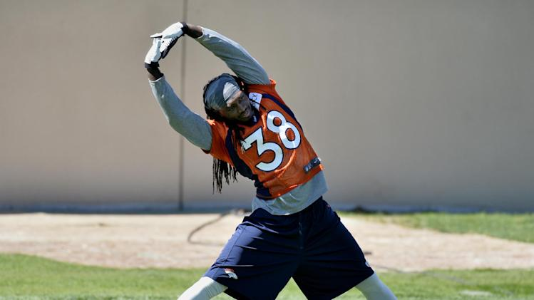 In this Wednesday, May 28, 2014 photo, Denver Broncos' Quinton Carter stretches during an NFL football organized team activity, in Englewood, Colo. Carter, who was on injured reserve last season, is back and turning heads at training camp