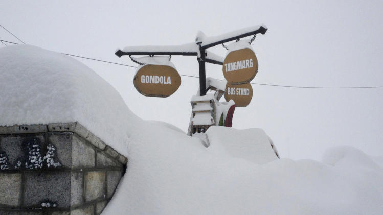 In this photo taken Wednesday, Feb. 27, 2013, signs are seen nearly buried in heavy snow in Gulmarg, Kashmir. Gulmarg, a ski resort nestled in the Himalayan mountains in Indian-held Kashmir is one of the most militarized places on earth.  (AP Photo/Kevin Frayer)