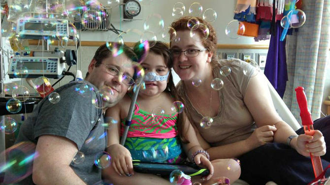FILE - In this May 30, 2013 file photo provided by the Murnaghan family, Sarah Murnaghan, center, celebrates the 100th day of her stay in Children's Hospital of Philadelphia with her father, Fran, left, and mother, Janet. The 10-year-old Pennsylvania girl, who underwent a double-lung transplant amid a national debate over the organ allocation process, has undergone a second transplant after the first failed and is now taking some breaths on her own, her parents said Friday, June 28, 2013. (AP Photo/Murnaghan Family, File)