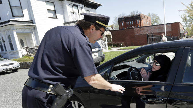 A police officer speaks with a woman in Muslim dress as she pulls into an entrance to the Graham, Putnam, at Mahoney Funeral Parlors in Worcester, Mass., Monday, May 6, 2013 where the body of killed Boston Marathon bombing suspect Tamerlan Tsarnaev is being prepared for burial. Funeral director Peter Stefan has pleaded for government officials to use their influence to convince a cemetery to bury Tsarnaev, but so far no state or federal authorities have stepped forward. (AP Photo/Elise Amendola)