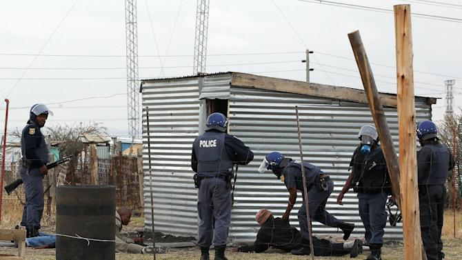 Police officers round up a group of men as they patrol the area near the Lonmin Platinum Mine near Rustenburg, South Africa, Saturday, Sept. 15, 2012. As various stakeholders continued negotiations South Africa Justice Minister Jeff Radebe warned that the Government would clamp down on daily illegal marches by miners brandishing machetes, spears and clubs that have marked the strike. (AP Photo/Themba Hadebe)
