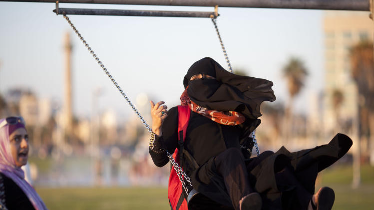 A Palestinian woman enjoys on a swing during the first day of the Eid al-Fitr holiday in Tel Aviv, Israel, Thursday, Aug. 8, 2013. The three-day holiday marks the end of the holy fasting month of Ramadan. One of the most important holidays in the Muslim world, Eid al-Fitr, is marked with prayers, family reunions and other festivities. (AP Photo/Ariel Schalit)