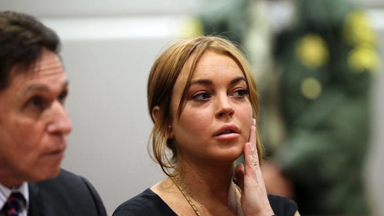 FILE - This Jan. 30, 2013 file photo shows actress Lindsay Lohan in Los Angeles court with her attorney Mark Heller, left, for a pretrial hearing in a case filed over the actress' June car crash. Lohan's case on charges she lied to police about her role in a June 2012 car crash returns to court on Friday March 1, 2013. (AP Photo/David McNew, Pool)