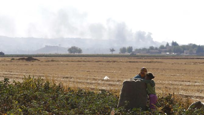 Smoke rises over Syrian town of Kobani as people collect cotton in Caykara