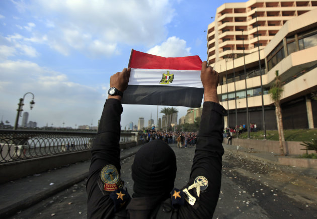 A police officer holds the Egyptian national flag during clashes with anti-government protesters, background, near Tahrir Square, Cairo, Egypt, Tuesday, Jan. 29, 2013. Intense fighting for days around