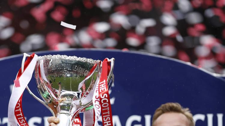 Aberdeen's Russell Anderson holds the trophy aloft following their Scottish League Cup final soccer match against Inverness Caledonian Thistle at Celtic Park Stadium, Glasgow, Scotland
