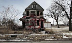 A vacant and blighted home, covered with red spray paint, sits alone in an east side neighborhood once full of homes in Detroit