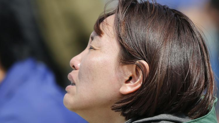 A family member of missing passengers who were on the South Korean passenger ferry Sewol which sank in the sea off Jindo, reacts as she looks toward the sea at a port in Jindo