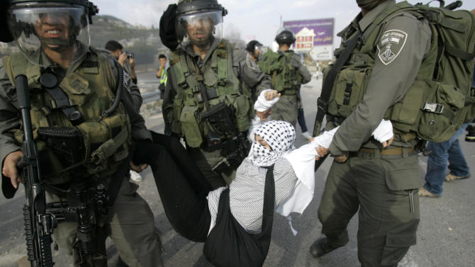 A Palestinian woman is arrested by Israeli security forces during a protest during against the Israeli military operations in Gaza Strip near the West Bank city of Nablus, Saturday, Nov. 17, 2012. (AP Photo/Nasser Ishtayeh)