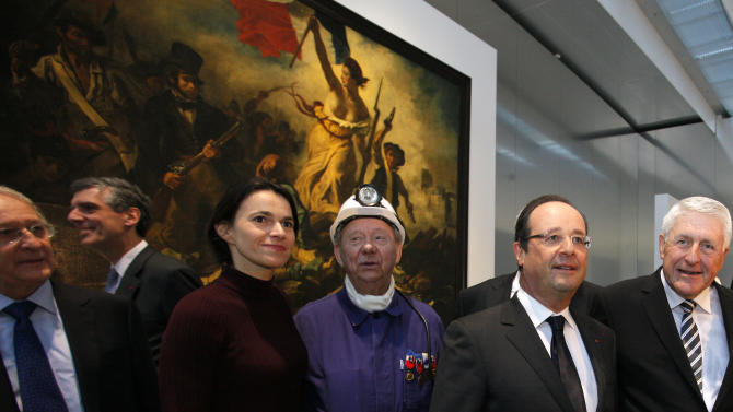 "France's President Francois Hollande, second right, is seen with  Culture minister Aurelie Filippetti, third left,  with a former miner, Lucien Laurent, centre in front of "" La Liberte Guidant le Peuple"", a painting by Eugene Delacroix during the inauguration of the Louvre Museum in Lens, northern France, Tuesday, Dec. 4, 2012. The museum in Lens is to open on Dec. 12, as part of a strategy to spread art beyond the traditional bastions of culture in Paris to new audiences in the provinces. (AP Photo/Michel Spingler Pool)"