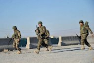 Afghan forces arrive at the site of a suicide attack in Jalalabad on December 2.Taliban insurgents launched a major suicide attack against a NATO base at an Afghan city airport, killing five people and wounding several foreign troops, officials said